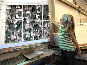 large electronic map with young girl photograph.